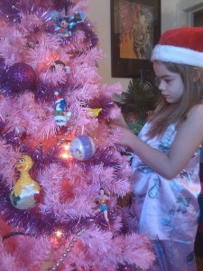 Mini Maven decorating our Pepto pink cartoon character Christmas tree in 2011 :)